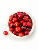 close up on a white bowl filled with raw cranberries on white background
