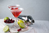 Cranberry martini in glasses on rustic background