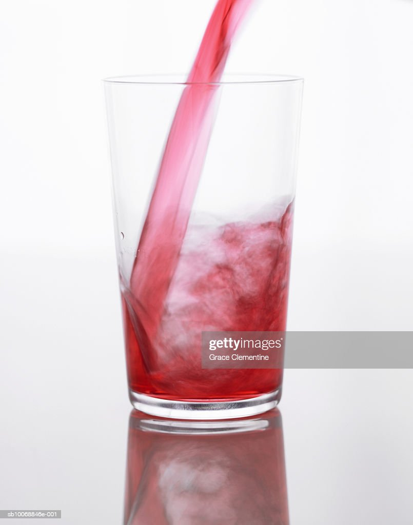 Cranberry juice pouring in glass, close-up
