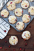 Cranberry Muffins  in a muffin tin with kitchen towel over a rustic wood  background with scattered fresh cranberries on the table.