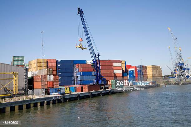 Crane and colorful containers stacked on quayside Port of Rotterdam Netherlands