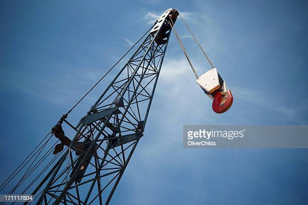 Crane boom and hook with sky background.