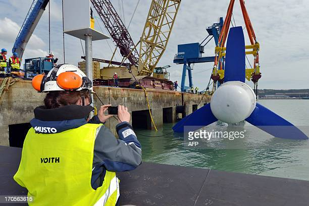 A crane carries the first HyTide underwater turbine built by German company Voith Hydro at Cherbourg's shipyard to put it in the water at Cherbourg's...