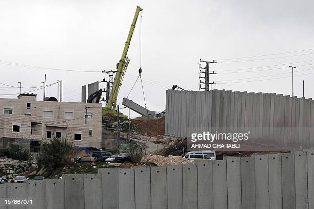 A crane completes a section of Israel's controversial separation barrier near Jerusalem's Shuafat refugee camp on December 5 2012 If Israel moves...