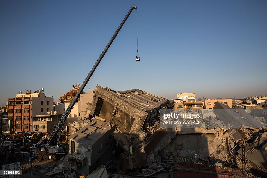 A crane is used in the rescue and search operations that continue at the site where a building complex which collapsed in the 6.4 magnitude earthquake, in the southern Taiwanese city of Tainan on February 8, 2016. Rescuers raced on February 7 to free around 120 people buried under the rubble of an apartment complex felled by an earthquake in southern Taiwan that left 34 confirmed dead, as an investigation began into the collapse. AFP PHOTO / ANTHONY WALLACE / AFP / ANTHONY WALLACE