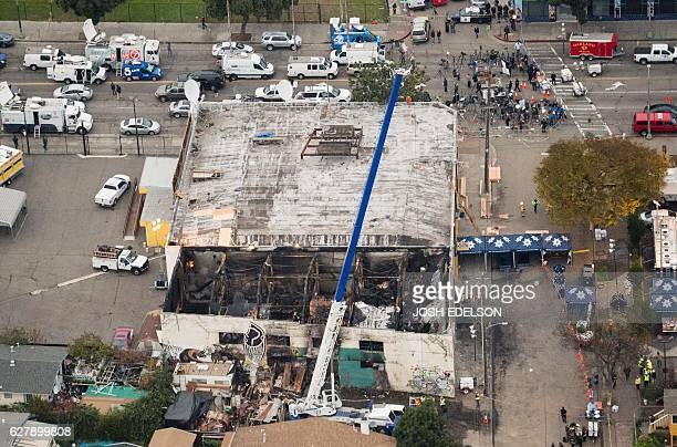 A crane is used to lift wreckage as part of search efforts in a fireravaged warehouse on December 05 2016 in Oakland California The death toll from a...