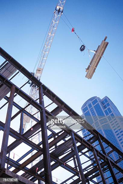 Crane lifting girders at construction site
