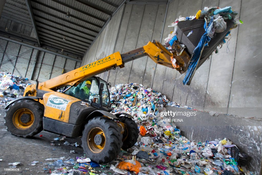 A crane lifts garbage at a waste treatment plant in Palma de Mallorca on January 17, 2013. AFP PHOTO/ Jaime REINA