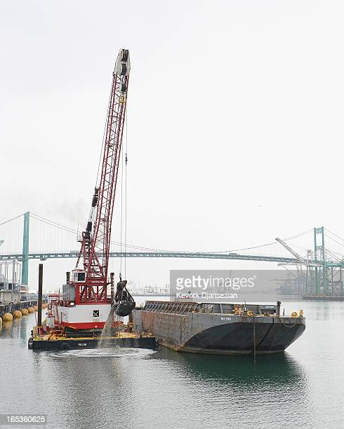 A crane lifts up the last ceremonial last scoop of dirt from the main navigational channel of Port of Los Angeles after completing of the port's main...