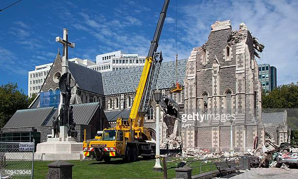 A crane lifts workers up to inspect the damaged Christchurch Cathedral in Christchurch on February 24 two days after a deadly earthquake rocked New...