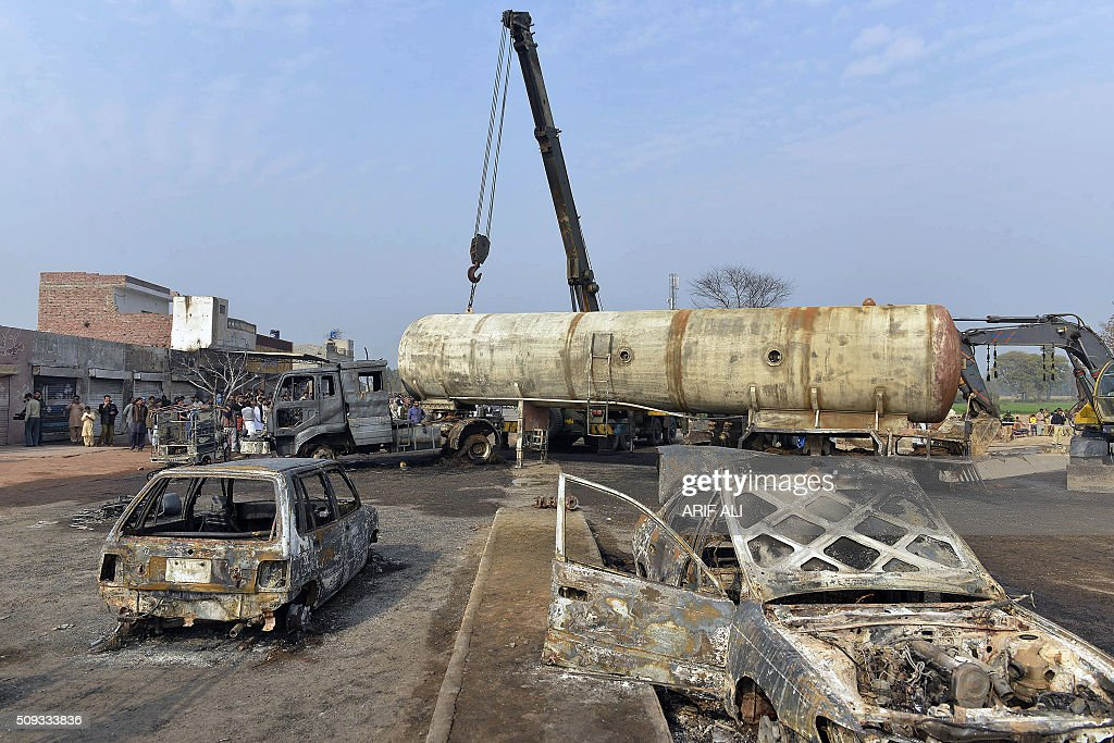 A crane lifts wreckage of a burnt out a tanker that collided with a car in the district of Sheikhupura in Pakistan's most populous Punjab province on February 10, 2016. Six schoolchildren were among at least 10 people killed when a fireball erupted as a tanker carrying liquefied petroleum gas (LPG) collided with a car in eastern Pakistan, engulfing surrounding vehicles, officials said. AFP PHOTO / ARIF ALI / AFP / Arif Ali