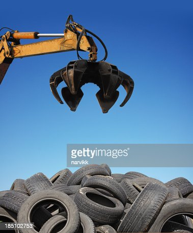 Crane loader taking old used tyres