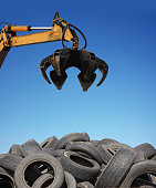 Crane loader taking old used tyres