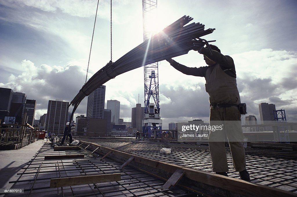Crane Lowering Girders to Two Builders : Stock Photo