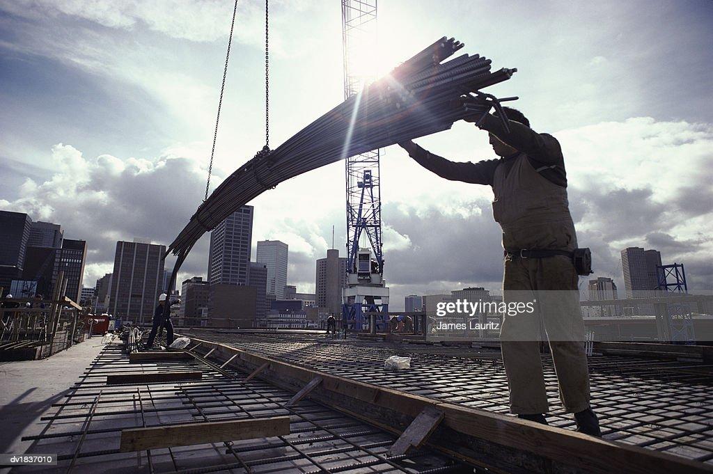Crane Lowering Girders to Two Builders