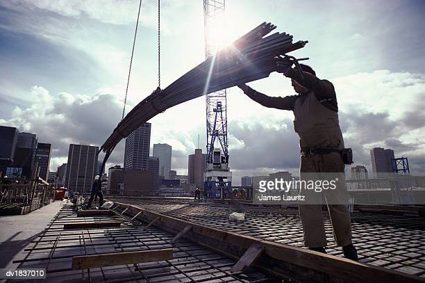 Crane Lowering Girders to Two Builders