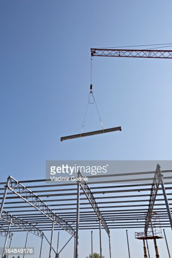 Crane lowering steel beam towards construction frame