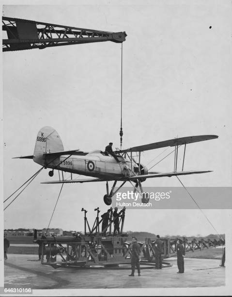 A crane lowers a biplane onto a catapult for launching Military personnel at this air station are being trained in the methods of launching aircraft...