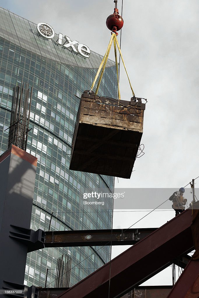 A crane lowers a load of building materials at the construction site of the BBVA Bancomer Tower in Mexico City, Mexico, on Thursday, Dec. 13, 2012. The office for BBVA Bancomer, the Mexican unit of Banco Bilbao Vizcaya Argentaria SA, Spain's second-biggest bank, will have 50 floors and accommodate about 4,500 employees when it is completed. Mexico City's famous Torre Mayor building stands in the background. Photographer: Susana Gonzalez/Bloomberg via Getty Images