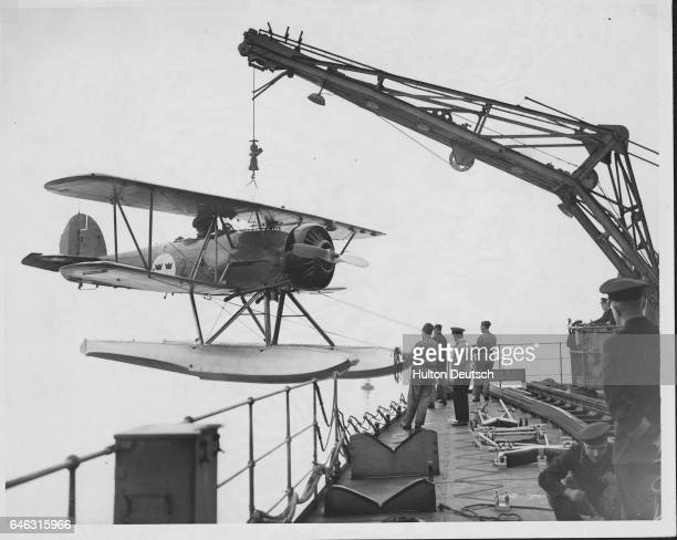 A crane lowers a seaplane from the deck of the Swedish ship HMS Gotland during a visit to Falmouth Cornwall England in 1937