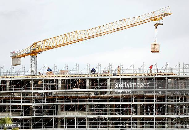 A crane maneuvers a pallet into position as builders work on a residential construction site in Rome Italy on Wednesday May 15 2013 The Italian...