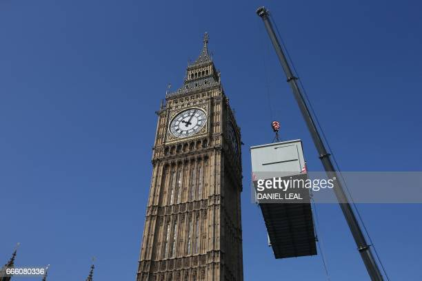 A crane manoeuvrers a Portakabin into Speakers Green at the foot of the Elizabeth Tower more commonly referred to as 'Big Ben' outside the Houses of...