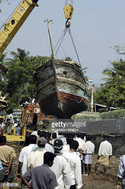 A crane removes a fishing trawler from a road at Nagapattinam port some 350 km south of Madras 29 December 2004 after tidal waves hit the region...