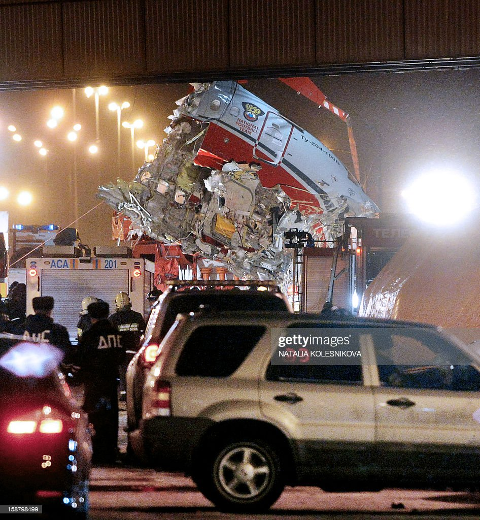 A crane removes the cabin of the Tu-204 jet from the crash site near the Vnukovo airport outside Moscow on December 29, 2012. Four crew were killed when a Russian airliner crashed into a motorway and broke up into three pieces after overshooting the runway at an international Moscow airport. The Red Wings airlines Russian-made Tu-204 jet -- empty of passengers and carrying just its eight crew on a return trip from the Czech Republic -- caught fire after crashing through the perimeter fence of Vnukovo airport in the west of the city. AFP PHOTO / NATALIA KOLESNIKOVA