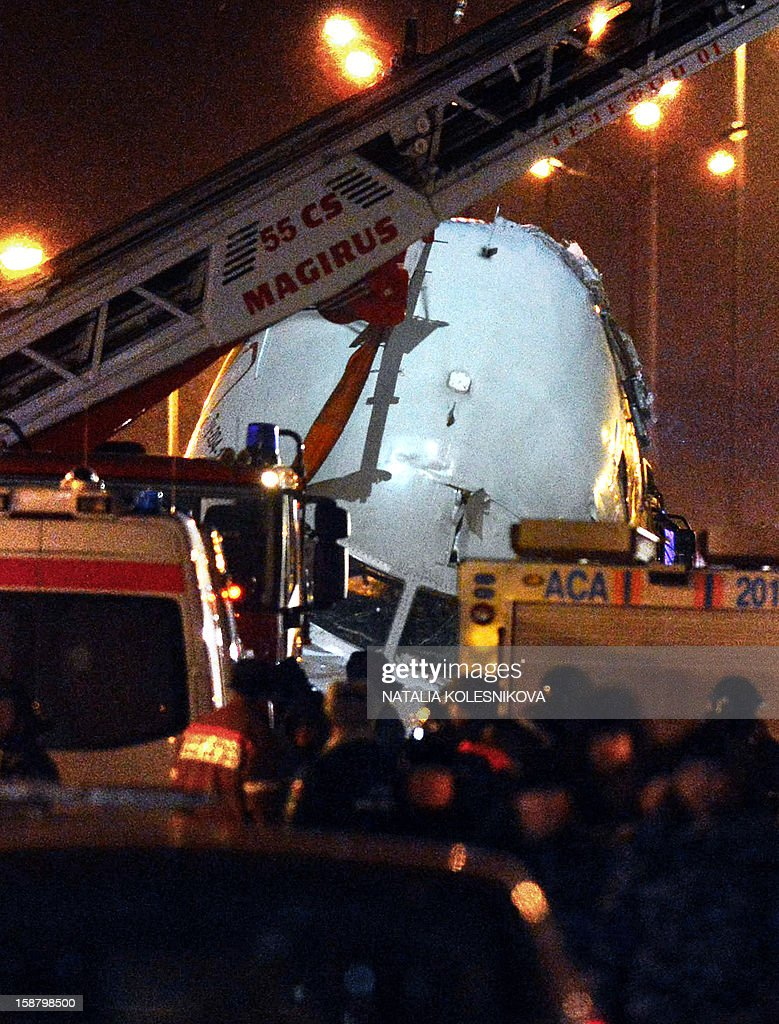 A crane removes the cabin of the Tu-204 jet from the crash site near the Vnukovo airport outside Moscow on December 29, 2012. Four crew were killed when a Russian airliner crashed into a motorway and broke up into three pieces after overshooting the runway at an international Moscow airport. The Red Wings airlines Russian-made Tu-204 jet -- empty of passengers and carrying just its eight crew on a return trip from the Czech Republic -- caught fire after crashing through the perimeter fence of Vnukovo airport in the west of the city.