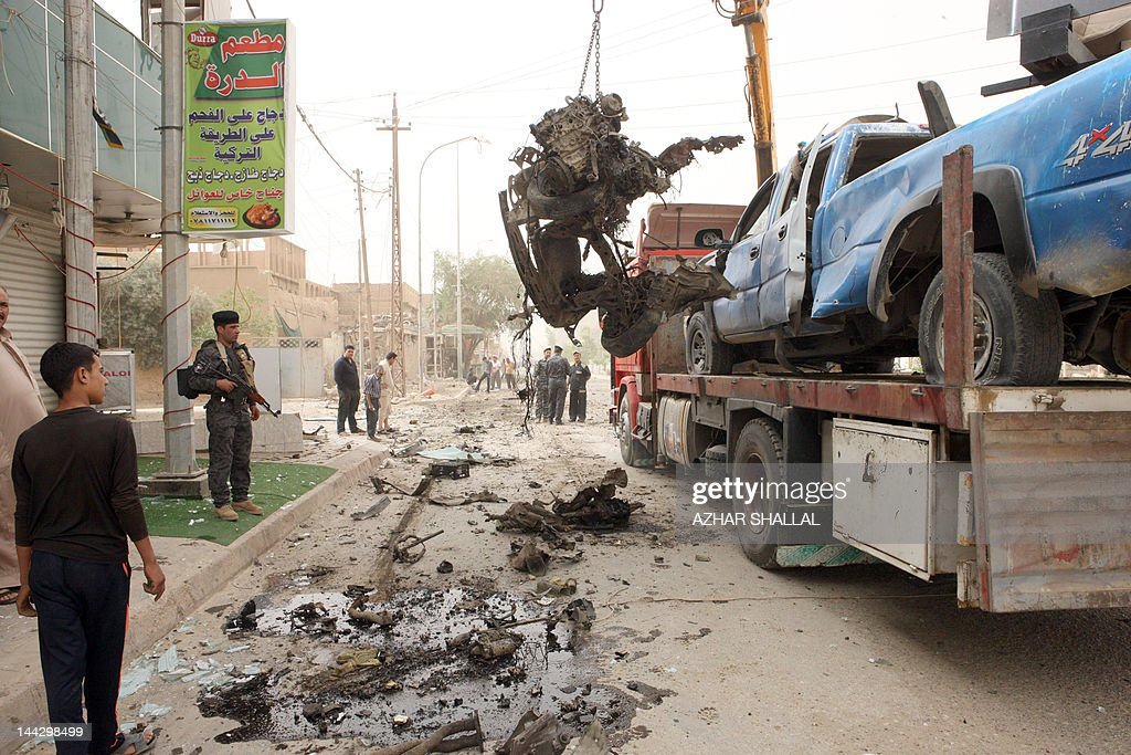 A crane removes the debris of a vehicle following a car bomb believed to be targeting a police patrol in the center of the city of Ramadi, Anbar provincial capital, in western Iraq, 100kms west of the capital Baghdad, on May 13, 2012, in which one person died and seven others were wounded according to medical sources.
