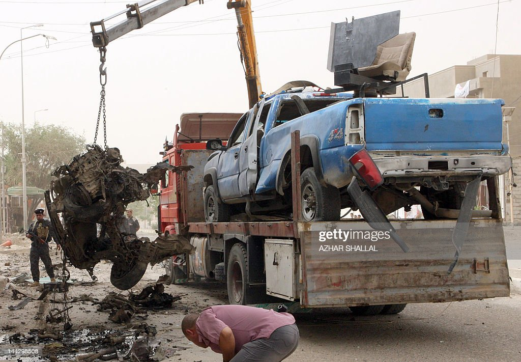 A crane removes the debris of a vehicle following a car bomb believed to be targeting a police patrol in the center of the city of Ramadi, Anbar provincial capital, in western Iraq, 100kms west of the capital Baghdad, on May 13, 2012, in which one [person died and seven others were wounded.