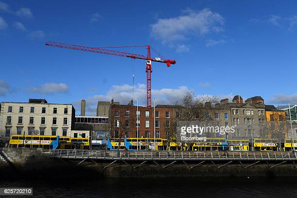 A crane stands above buses passing alongside the River Liffey in Dublin Ireland on Thursday Nov 24 2016 Irish ministers and executives are closely...