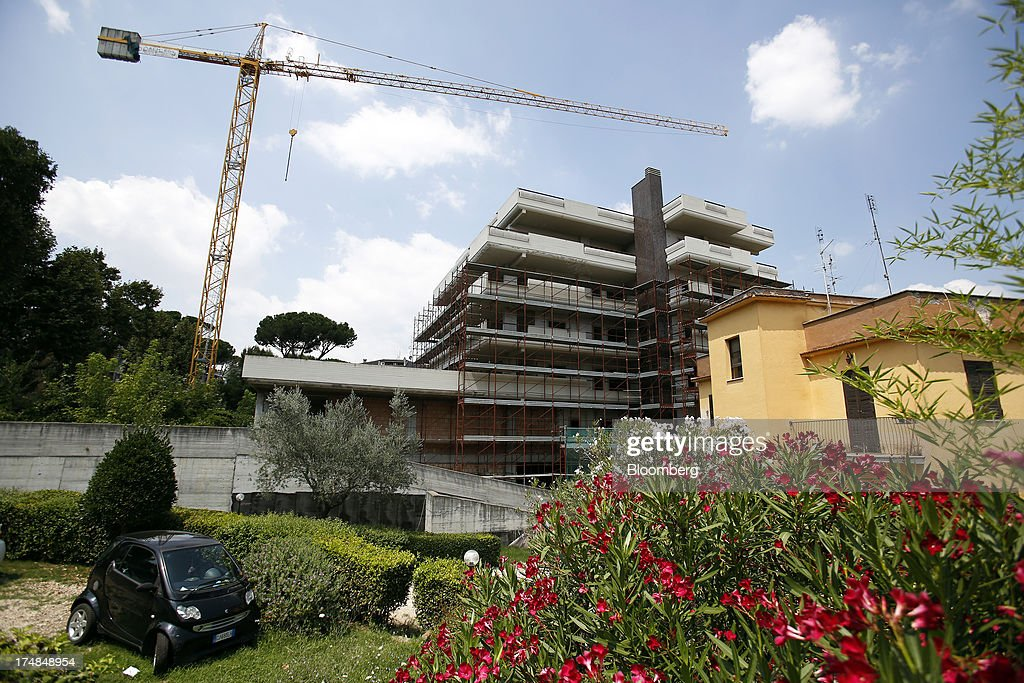 A crane stands on a residential construction site as a smart car sits parked in a neighboring garden in Rome, Italy, on Saturday, July 27, 2013. Italy's home prices are low enough to trigger an increase in purchases for the first time since 2006, though that won't lift values for at least two years, according to the Nomisma institute. Photographer: Alessia Pierdomenico/Bloomberg via Getty Images