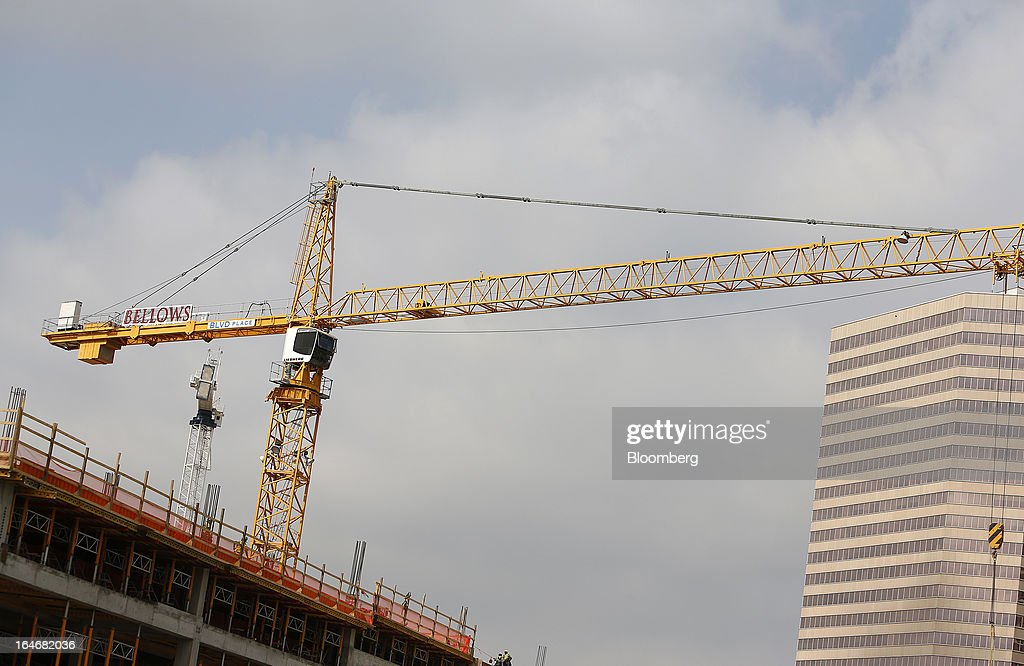 A crane stands on the top of a building under construction in Houston, Texas, U.S., on Monday, March 18, 2013. Office sales in Houston, the fourth-largest U.S. city, jumped 32 percent last year to $3.89 billion, the highest total in five years and outpacing the 21 percent gain for the entire U.S., according to the research firm Real Capital Analytics. Photographer: Aaron M. Sprecher/Bloomberg via Getty Images