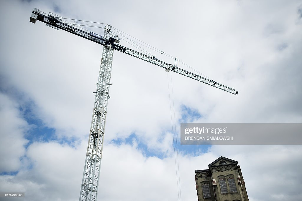 A crane towers above a commercial construction adjacent to an historic building that was spared demolition, May 2, 2013 in Washington, DC. AFP PHOTO/Brendan SMIALOWSKI