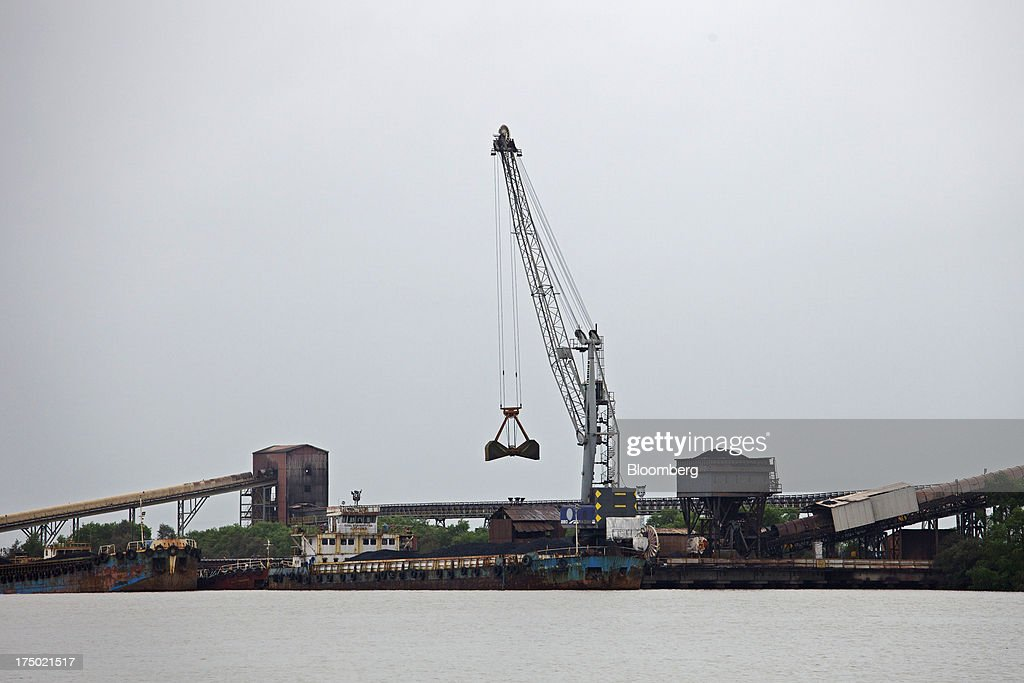 A crane unloads from a mini-bulk carrier ship moored at the JSW Steel Ltd. jetty, operated by JSW Dharamtar Port Pvt. Ltd, near JSW Steel's manufacturing facility in Dolvi, Maharashtra, India, on Friday, July 27, 2013. JSW Steel is scheduled to announce first-quarter earnings on July 31. Photographer: Adeel Halim/Bloomberg via Getty Images