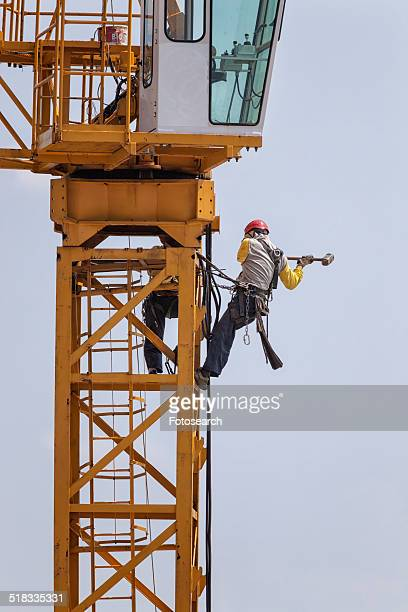 Crane with two men wearing yellow jackets