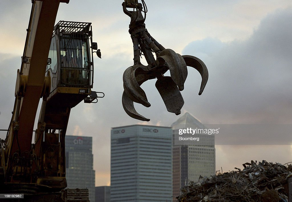 A crane works at a metal recycling yard operated by European Metal Recycling Ltd., against a backdrop of Canary Wharf and the offices of Citigroup Inc., left, HSBC Holdings Plc, center, and 1 Canada Square in London, U.K., on Monday, Dec. 10, 2012. HSBC Holdings Plc, Europe's largest bank, agreed to pay $1.92 billion to settle U.S. probes of money laundering in the largest such accord ever. Photographer: Jason Alden/Bloomberg via Getty Images