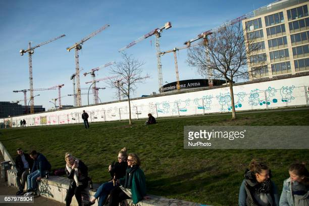 Cranes and the MercedesBenz Arena are seen from the park of the East Side Gallery as people enjoy the first spring sun in the district of...