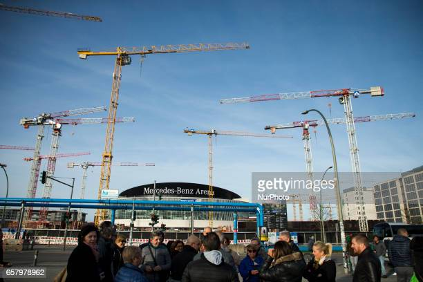 Cranes and the MercedesBenz Arena are seen from the park of the East Side Gallery as a group of tourists enjoy the first spring sun in the district...