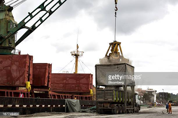 Cranes are seen unloading 'Clinker' from a bulk carrier ship and into waiting trucks on the dockside at Mombasa port managed by the Kenya Ports...