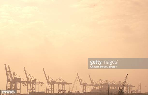 Cranes At Harbor Against Sky During Foggy Weather