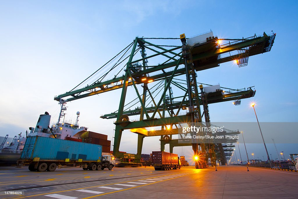 Cranes, cargo containers and trucks at a shipping port during dusk : Stock Photo