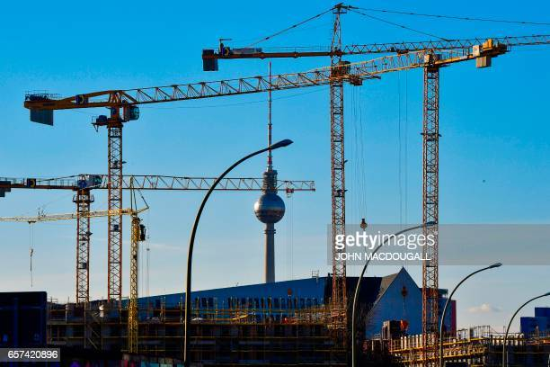 Cranes frame Berlin's TV Tower at a constrution site near the city's famed East Side gallery on March 24 2017 / AFP PHOTO / John MACDOUGALL