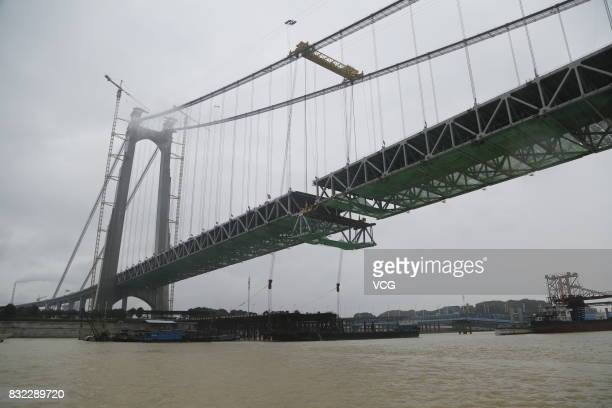 Cranes lift the steel truss girder to connect the the 2390meterlong Dongting Lake Bridge on the HangzhouRuili expressway on August 14 2017 in Yueyang...