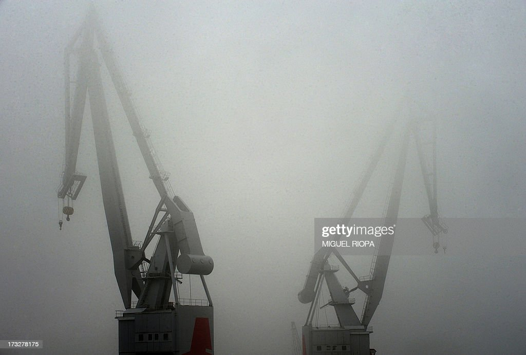 Cranes of the shipyard 'Vulcano' are pictured in the fog of Vigo, on July 11, 2013. AFP PHOTO/ MIGUEL RIOPA