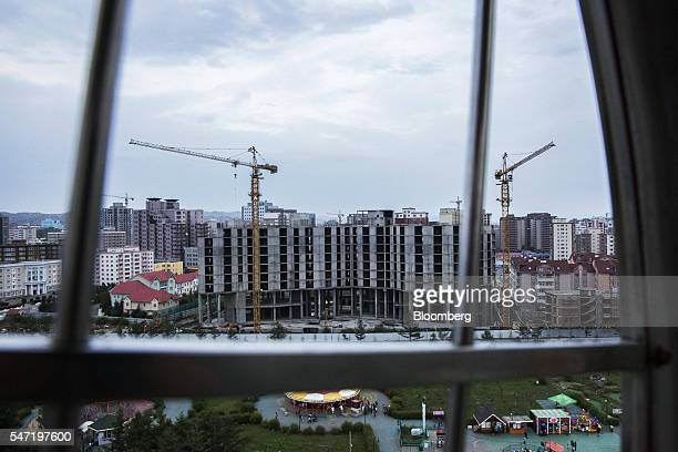 Cranes operate at a construction site next to the National Amusement Park known as the Children's Park in Ulaanbaatar Mongolia on Wednesday July 13...
