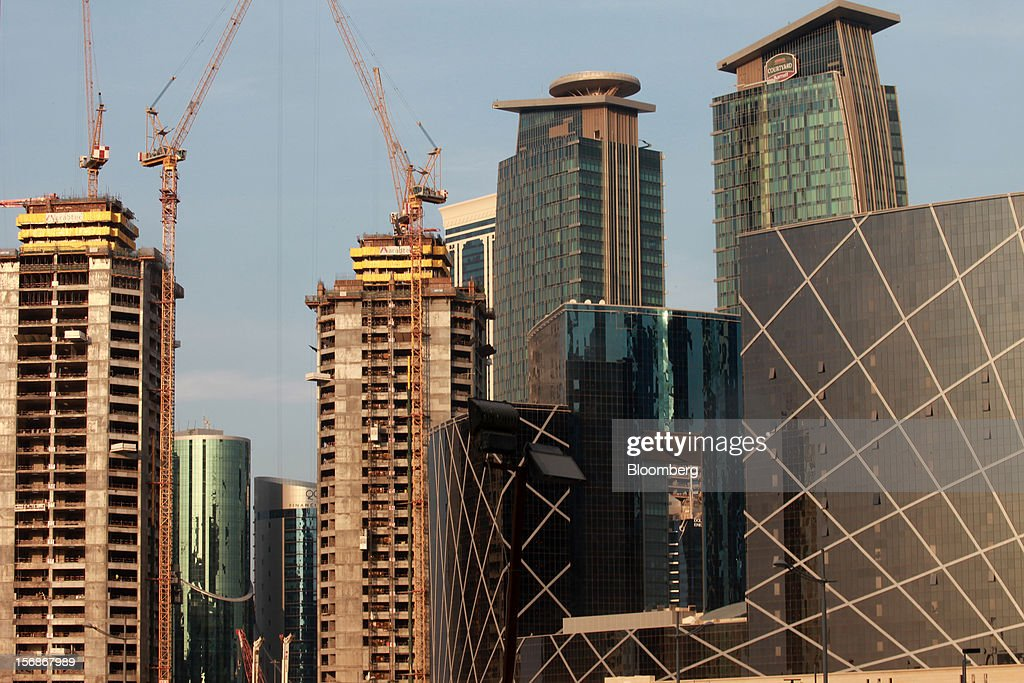 Cranes operate beside new high-rise buildings under construction in Doha, Qatar, on Thursday, Nov. 22, 2012. Qatar Telecom QSC, the country's biggest company by revenue, is seeking a syndicated loan for about $1 billion to refinance existing debt, according to a person with direct knowledge of the deal. Photographer: Gabriela Maj/Bloomberg via Getty Images