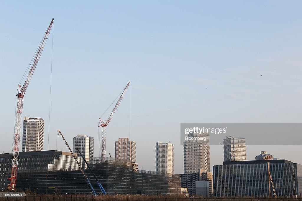Cranes operate on a construction site for a hospital, left, in Tokyo, Japan, on Tuesday, Jan. 8, 2013. Prime Minister Shinzo Abe aims to compile Japan's economic stimulus package on Jan. 11, and seeks to have new economic growth strategy by mid-year. Photographer: Kiyoshi Ota/Bloomberg via Getty Images