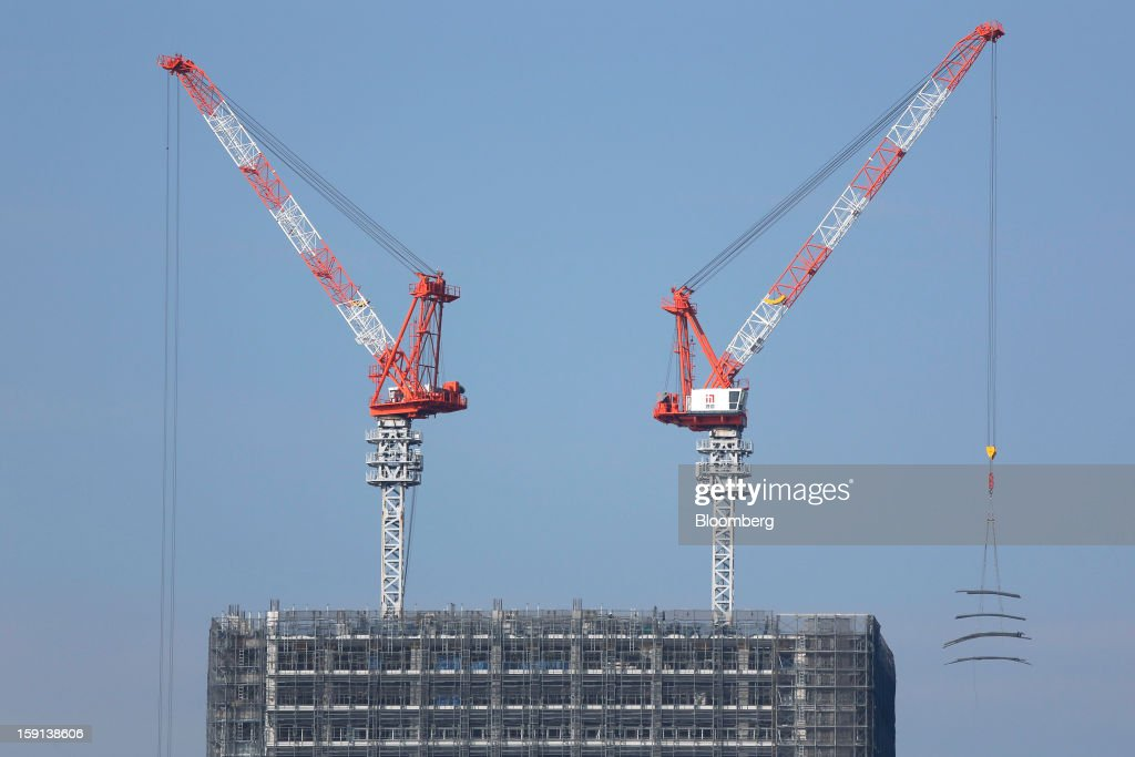 Cranes operate on a construction site in Tokyo, Japan, on Tuesday, Jan. 8, 2013. Prime Minister Shinzo Abe aims to compile Japan's economic stimulus package on Jan. 11, and seeks to have new economic growth strategy by mid-year. Photographer: Kiyoshi Ota/Bloomberg via Getty Images